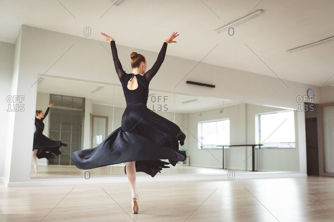Caucasian attractive female ballet dancer with red hair dancing ballet, wearing a black, long dress, preparing for a ballet class in a bright studio, focusing on her exercise.