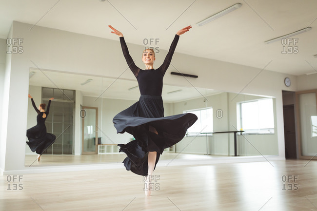 Caucasian attractive female ballet dancer with red hair dancing ballet, wearing a black, long dress, preparing for a ballet class in a bright studio, focusing on her exercise, smiling.