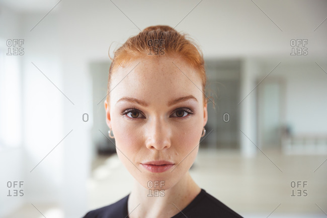Portrait of a Caucasian attractive female ballet dancer with red hair preparing for a ballet class in a bright studio, staring to camera with a slight smile