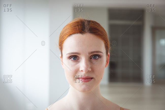 Portrait of a Caucasian attractive female ballet dancer with red hair preparing for a ballet class in a bright studio, staring to camera with a smile on her face.