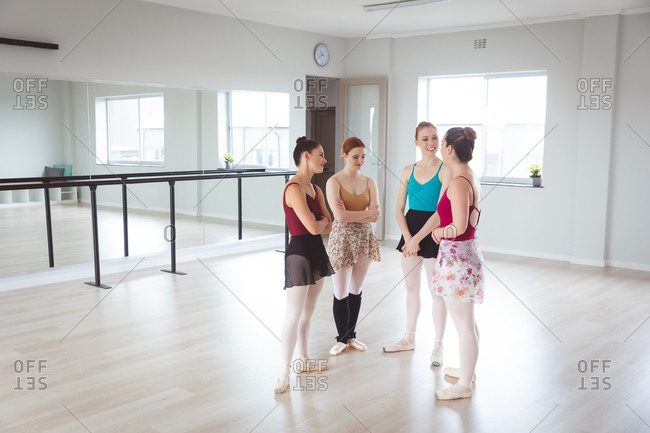 A group of Caucasian female attractive ballet dancers having a conversation in a bright ballet studio, looking happy, preparing for a ballet class.