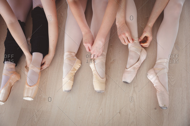 Low section of a group of Caucasian female ballet dancers tying their ballet shoes in a bright ballet studio, preparing for a ballet class, sitting on the floor.