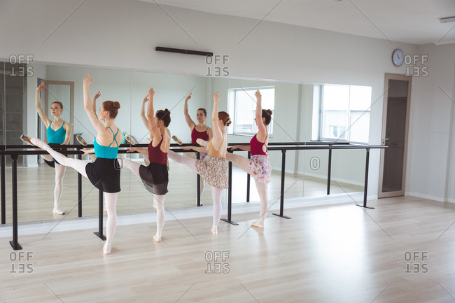 A group of Caucasian female attractive ballet dancers stretching out, holding a barre in a bright ballet studio, focused on their exercise, preparing for a ballet class.