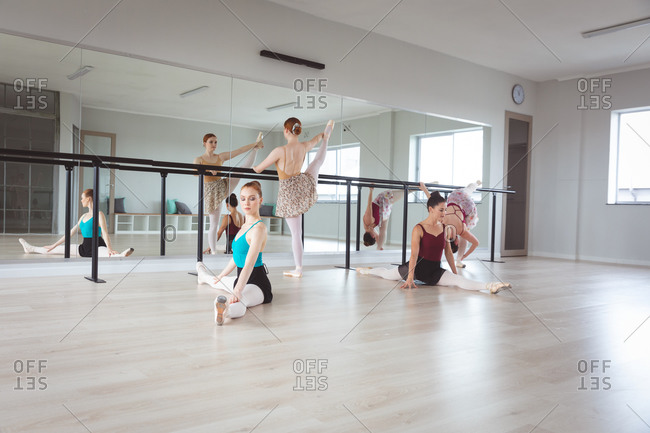 A group of Caucasian female attractive ballet dancers warming up, holding a barre and stretching on the floor in a bright ballet studio, focused on their exercise, preparing for a ballet class.