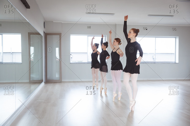 A group of Caucasian female attractive ballet dancers in black suits practicing during a ballet class in a bright studio, dancing in front of a mirror.