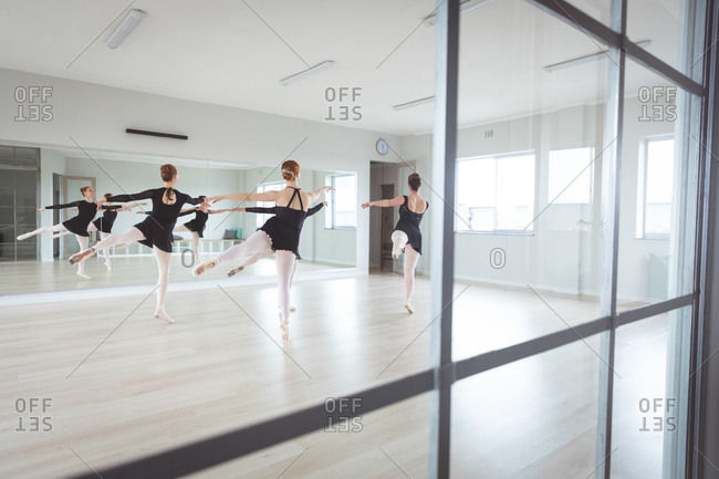 A group of Caucasian female ballet dancers in black outfits practicing during a ballet class dancing in front of a mirror in a bright studio, seen through a window.