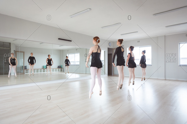 A group of Caucasian female attractive ballet dancers in black suits practicing during a ballet class in a bright studio, dancing in front of a mirror, jumping in unison