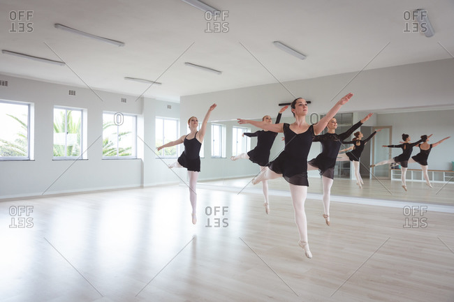 A group of Caucasian female attractive ballet dancers in black outfits practicing during a ballet class in a bright studio, dancing and jumping on one leg in unison.