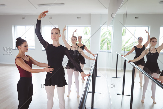 A Caucasian female ballet teacher working with a group of Caucasian female dancers during a ballet class in a bright studio, the dancers holding the barre while the teacher works on their posture.
