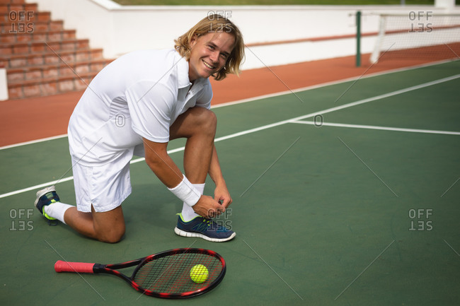 Portrait of a Caucasian man wearing tennis whites spending time on a court playing tennis on a sunny day, tying shoe laces, looking at camera and smiling