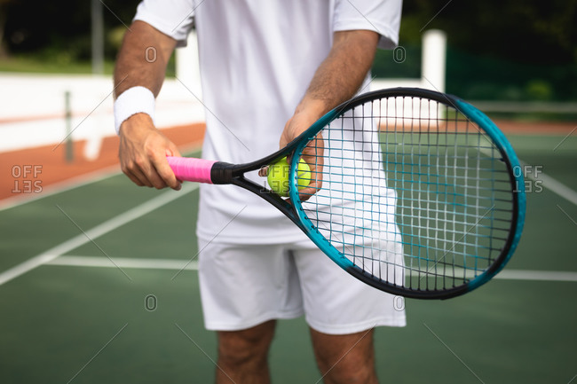 Mid section of a Caucasian man wearing tennis whites spending time on a court playing tennis on a sunny day, holding a tennis racket and a ball