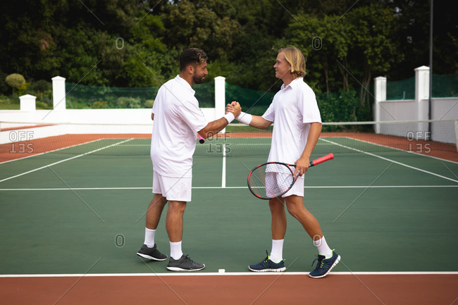 A Caucasian and a mixed race men wearing tennis whites spending time on a court together, playing tennis on a sunny day, shaking hands, one of them holding a tennis racket