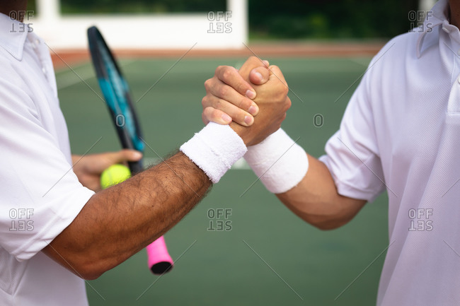 Mid section close up of a Caucasian and a mixed race men wearing tennis whites spending time on a court together, playing tennis on a sunny day, shaking hands, one of them holding a tennis racket