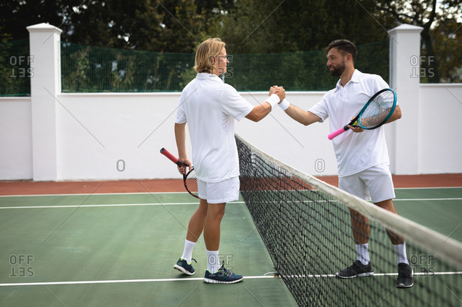 A Caucasian and a mixed race men wearing tennis whites spending time on a court together, playing tennis on a sunny day, shaking hands, holding a tennis rackets