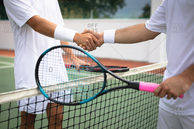 Mid section close up of a Caucasian and a mixed race men wearing tennis whites spending time on a court together, playing tennis on a sunny day, shaking hands, holding a tennis rackets