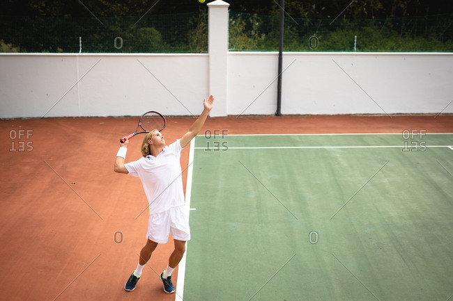 A Caucasian man wearing tennis whites spending time on a court playing tennis on a sunny day, holding a tennis racket and preparing to hit a ball