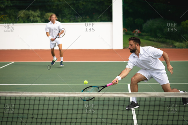 A Caucasian and a mixed race men wearing tennis whites spending time on a court together, playing tennis on a sunny day, holding tennis, one of them hitting a ball
