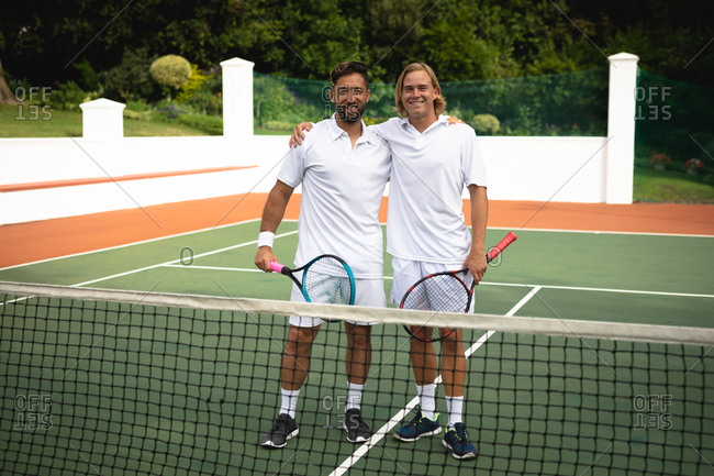 Portrait of a Caucasian and a mixed race men wearing tennis whites spending time on a court together, playing tennis on a sunny day, embracing, holding tennis rackets, looking at camera and smiling