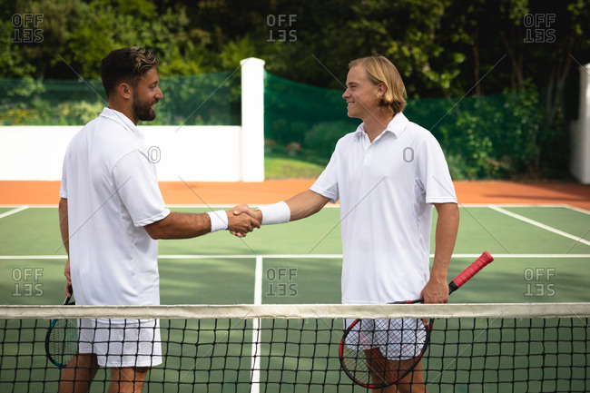 A Caucasian and a mixed race men wearing tennis whites spending time on a court together, playing tennis on a sunny day, shaking hands, one of them holding a tennis rackets