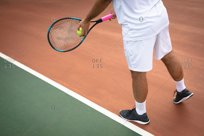 Mid section of a mixed race man wearing tennis whites spending time on a court playing tennis on a sunny day, holding a tennis racket and preparing to hit a ball