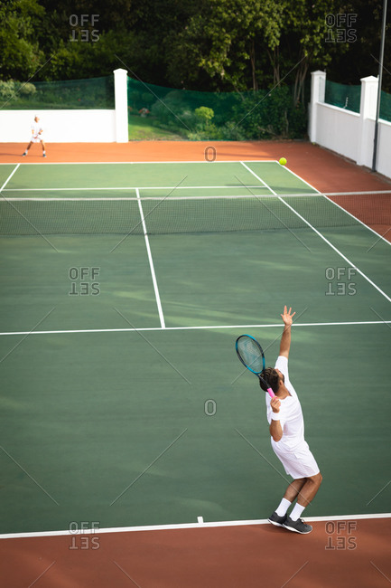 A Caucasian and a mixed race men wearing tennis whites spending time on a court together, playing tennis on a sunny day, one of them preparing to hit a ball