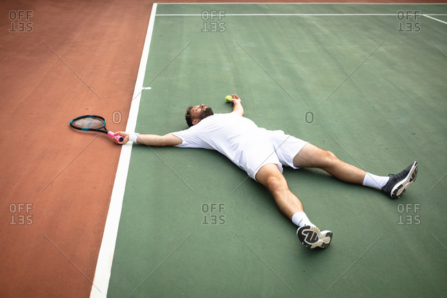 A mixed race man wearing tennis whites spending time on a court playing tennis on a sunny day, lying on a ground, holding a tennis racket and a ball