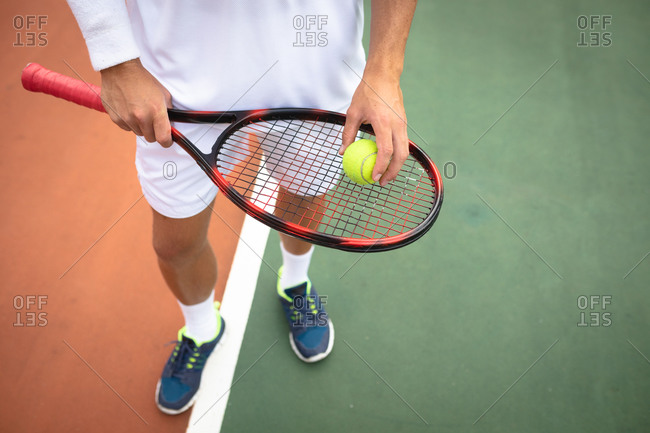 Mid section view of a mixed race man wearing tennis whites spending time on a court playing tennis on a sunny day, holding a tennis racket and a ball