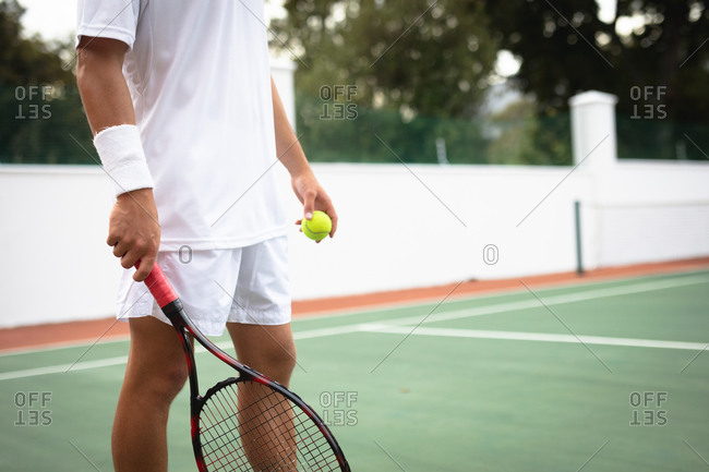 Mid section of a Caucasian man wearing tennis whites spending time on a court playing tennis on a sunny day, holding a tennis racket, preparing to hit a ball