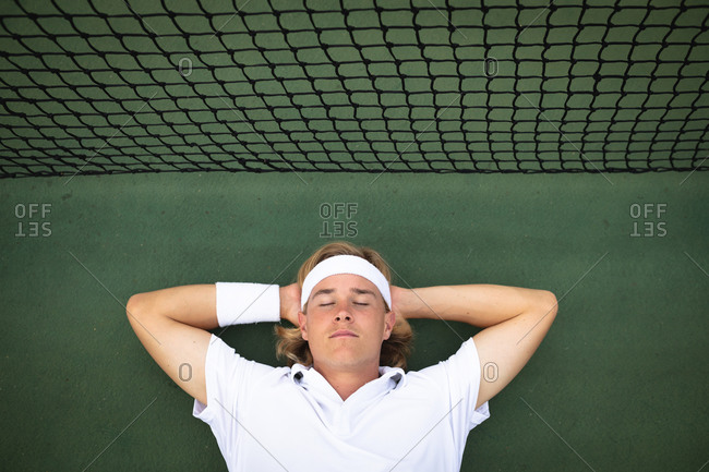 A Caucasian man wearing tennis whites spending time on a court playing tennis on a sunny day, lying on a ground with his eyes closed next to a net
