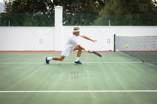 A Caucasian man wearing tennis whites spending time on a court playing tennis on a sunny day, holding a tennis racket, preparing to hit a ball