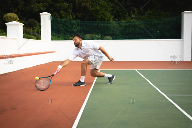 A mixed race man wearing tennis whites spending time on a court playing tennis on a sunny day, hitting a ball with a tennis racket