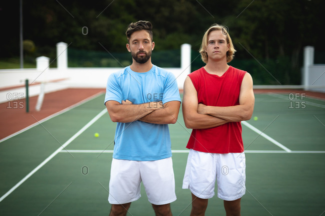 Portrait of a Caucasian and a mixed race men spending time on a court together, playing tennis on a sunny day, with their arms crossed, looking at camera
