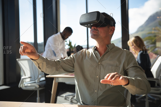 A Caucasian businessman working in a modern office, wearing VR headset, touching virtual interactive screen, with his colleagues working in the background