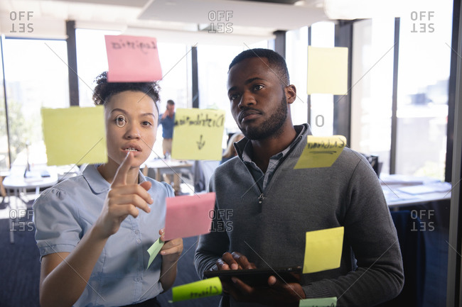 A mixed race businesswoman and an African American businessman working in a modern office, brainstorming writing on clear board with memo notes, seen through