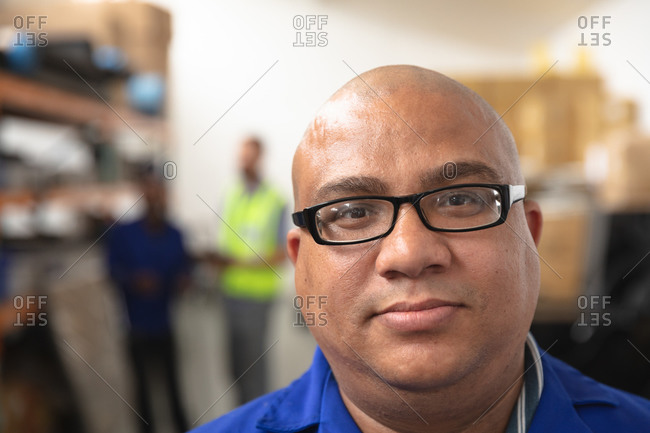 Portrait of a mixed race male worker wearing glasses in a storage warehouse at a factory making wheelchairs, looking at camera