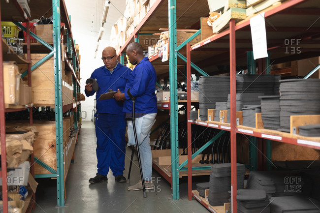 Mixed race and African American male workers in a storage warehouse at a factory making wheelchairs, standing and inspecting parts on shelves