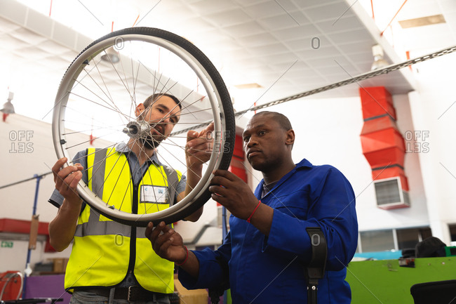 An African American male worker and a Caucasian male supervisor in the workshop at a factory making wheelchairs, standing and inspecting a wheel together, wearing a workwear