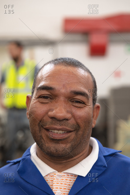 Portrait of an mixed race male worker wearing a workwear, in a storage warehouse at a factory making wheelchairs, looking at camera and smiling