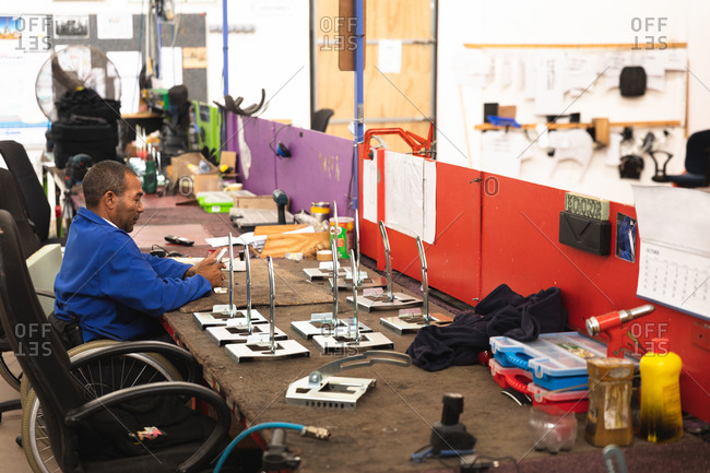 A disabled African American male worker in a workshop at a factory making wheelchairs, sitting at a workbench assembling parts of a product, sitting in wheelchair