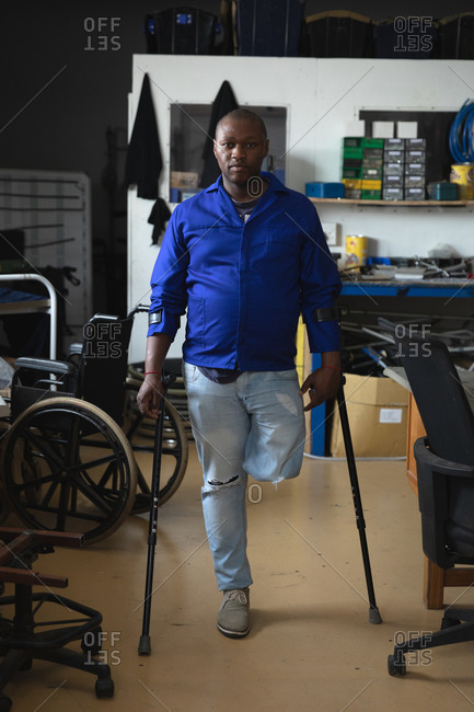 Portrait of a disabled African American male worker with one leg standing using crutches wearing workwear, in a storage warehouse at a factory making wheelchairs, looking at camera