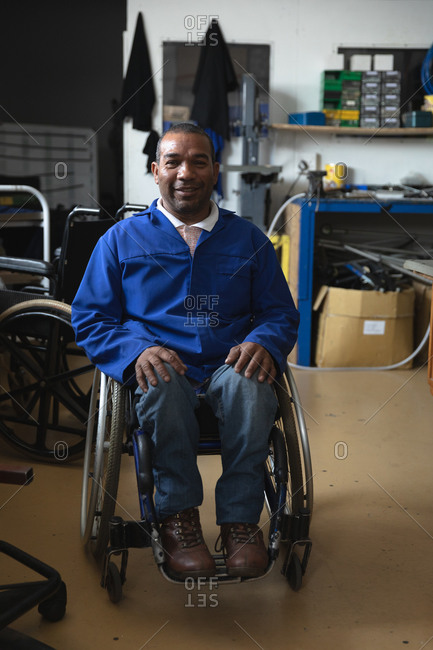 Portrait of a disabled mixed race male worker wearing workwear, in a storage warehouse at a factory making wheelchairs, looking at camera and sitting in wheelchair