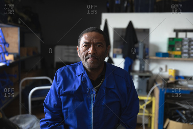 Portrait of an African American male worker wearing a workwear, in a storage warehouse at a factory making wheelchairs, looking at camera