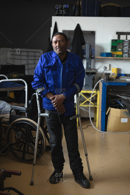 Portrait of a disabled African American male worker standing using crutches, wearing workwear, in a storage warehouse at a factory making wheelchairs, looking at camera