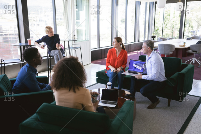Multi-ethnic group of male and female colleagues working in a modern office, meeting in a lounge area discussing business and their work