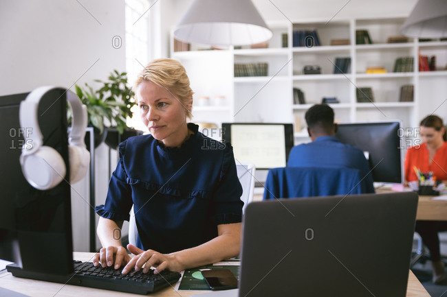 A Caucasian businesswoman working in a modern office, sitting at a desk and using a computer, with her business colleagues working in the background