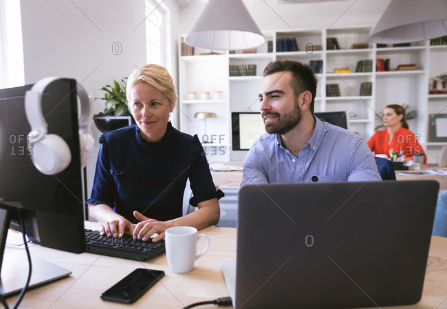 A smiling Caucasian businesswoman and businessman working in a modern office, using a computer and talking, with their business colleagues working in the background