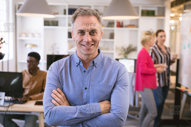 Portrait of a happy Caucasian businessman working in a modern office, looking at camera and smiling, with his business colleagues working in the background