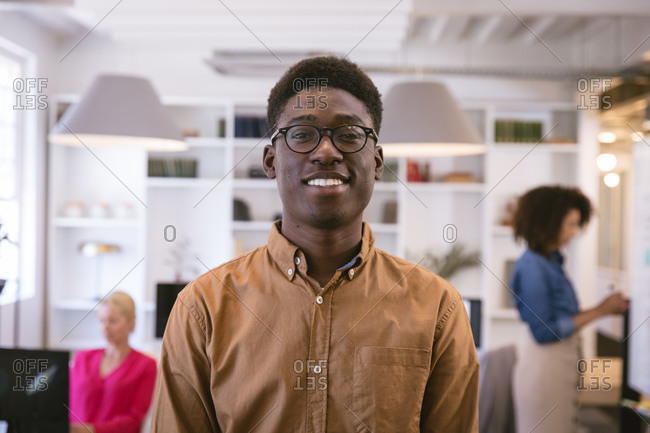 Portrait of a happy African American businessman working in a modern office, looking at camera and smiling, with his business colleagues working in the background