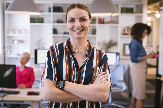 Portrait of a happy Caucasian businesswoman working in a modern office, looking at camera and smiling, standing with arms crossed, with her business colleagues working in the background