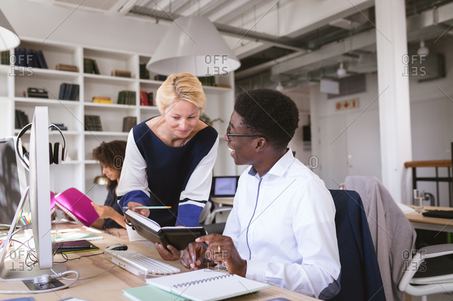 A happy Caucasian businesswoman and an African American businessman working in a modern office, talking, the woman holding a notebook, with their business colleagues working in the background